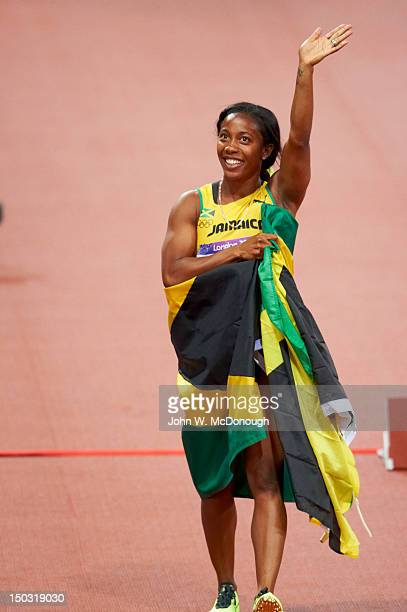 2012 Summer Olympics Jamaica ShellyAnn FraserPryce victorious with national flag after winning gold during Women's 100M Final at Olympic Stadium...