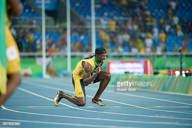 2016 Summer Olympics Jamaica Usain Bolt victorious down on one knee on track after winning gold medal in Men's 4x100M Relay Final at Rio Olympic...