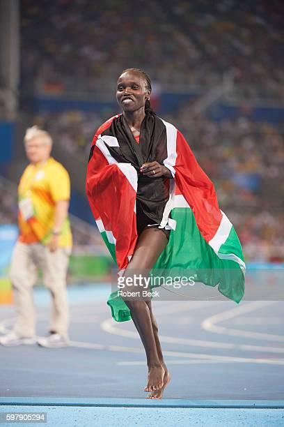 2016 Summer Olympics Kenya Vivian Cheruiyot victorious wearing Kenyan flag after winning gold medal in Women's 5000M Final at Rio Olympic Stadium Rio...