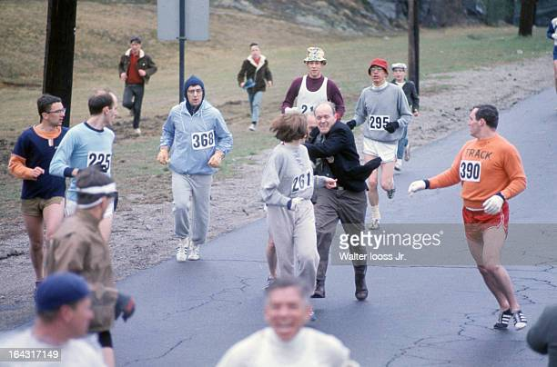 Boston Marathon USA Kathrine Switzer in action as BAA codirector Jock Semple attempts to tear off Switzer's bib during race on Union Street Switzer's...