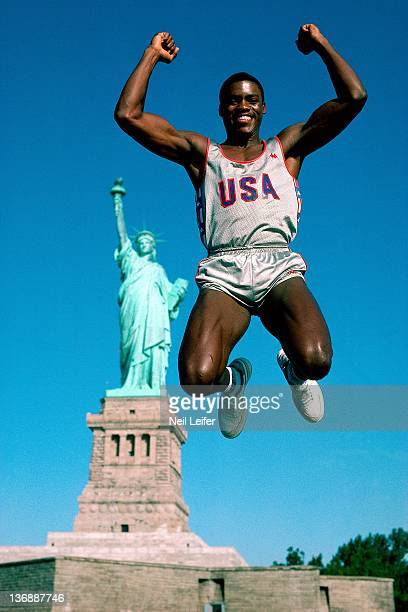 Track Field Summer Games Preview Portrait of USA Carl Lewis jumping in front of Statue of Liberty on Liberty Island in New York Harbor New York NY...