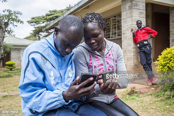 Summer Games Preview: View of Refugee Olympic Team James Nyang Chiengjiek and Rose Nathike Lokonyen on their cell phones at the Tegla Lorupe Training...