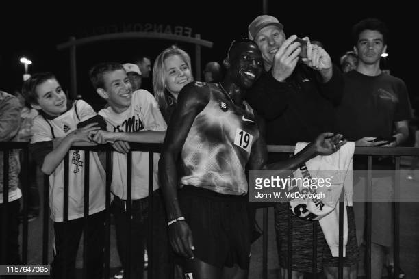 Sunset Tour View of Lopez Lomong taking photos with fans after Men's 5K race at Azusa Pacific University Cougar Stadium Azusa CA CREDIT John W...