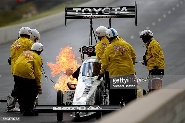 Track firefighters work to put out a fire on Top Fuel driver Antron Brown's car after a qualifying run during day two of the NHRA Mile High Nationals...