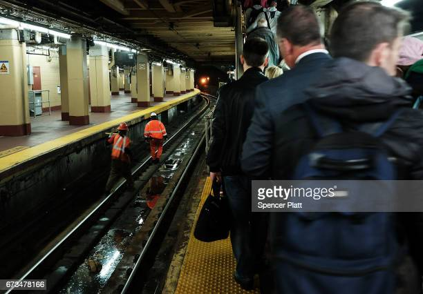 Track maintenance workers walk along train tracks used by both New Jersey Transit and Amtrak trains at Pennsylvania Station on April 26 2017 in New...