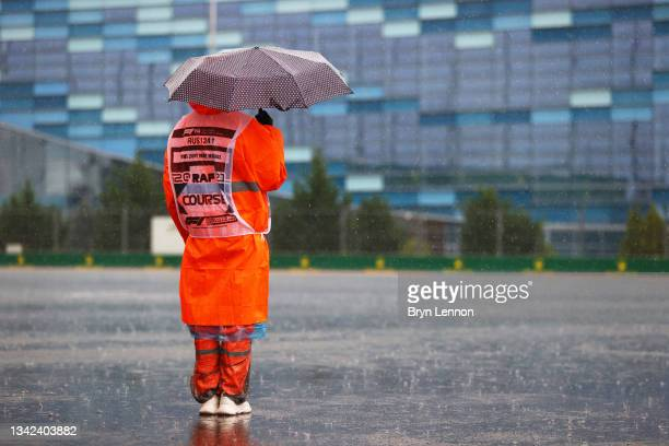 Track marshal shelters under an umbrella before final practice ahead of the F1 Grand Prix of Russia at Sochi Autodrom on September 25, 2021 in Sochi,...