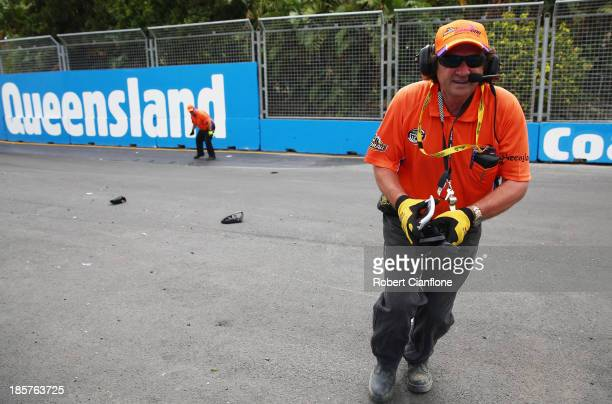 A track marshall removes pieces of broken side mirrors from the track during practice for the Gold Coast 600 which is round 12 of the V8 Supercars...