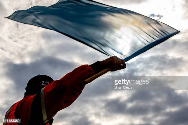 Track marshall waves a blue flag at competitors during the 24 Hours of Le Mans on June 18, 2016 in Le Mans, France.