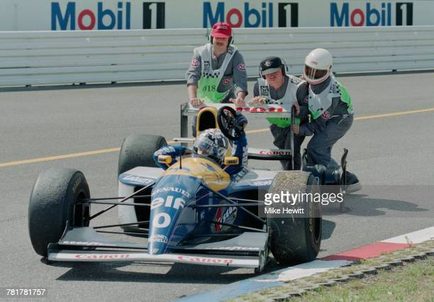 Track marshals attempt to push Damon Hill driver of the Canon Williams Renault Williams FW15C Renault V10 after he pulls off the track with a broken...