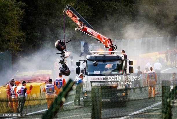 Track marshals look on as a crane lift parts of the damaged car of Sauber's Ecuadorian driver Juan Manuel Correa onto a truck following a serious...