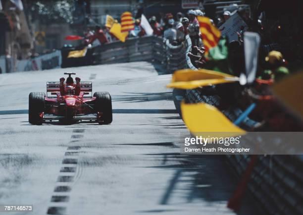 Track marshals wave their warning flags in salute as Michael Schumacher of Germany driving the Scuderia Ferrari Marlboro Ferrari F399 Ferrari V10...