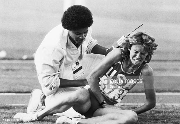 Track official attempts to comfort a crying Mary Decker after Decker's fall in the women's 3000-meter run at the 1984 Summer Olympics. Decker fell...