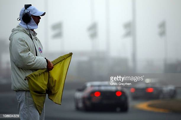 Track official watches as cars race under caution in dense fog during the Rolex 24 at Daytona International Speedway on January 30, 2011 in Daytona...