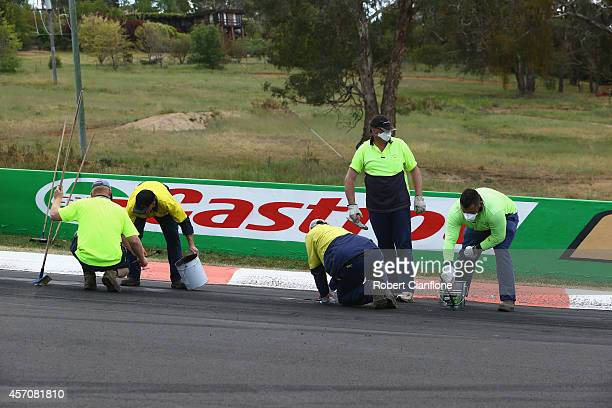 Track officials look to repair the track at turn two after the race was stopped during the Bathurst 1000 which is round 11 and race 30 of the V8...