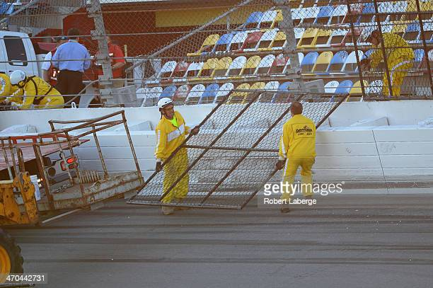 Track officials work on damage to the SAFER barrier and fence following an incident during practice for the NASCAR Sprint Cup Series Daytona 500 at...