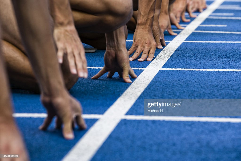 Track sprinters lined up at starting : Stock Photo