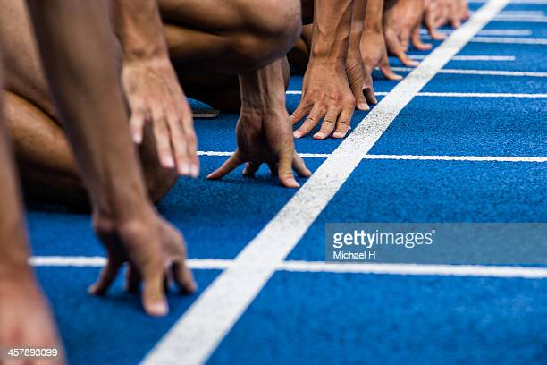 track sprinters lined up at starting - contest stock pictures, royalty-free photos & images