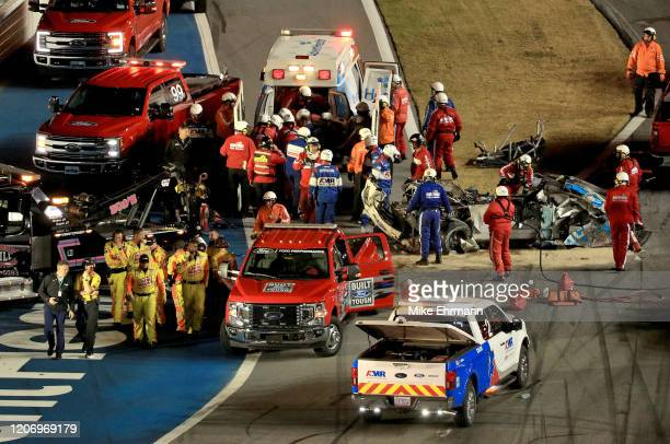 Track workers attend to Ryan Newman driver of the Koch Industries Ford following a crash during the NASCAR Cup Series 62nd Annual Daytona 500 at...