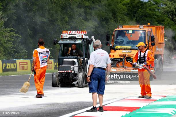 Track workers clean the track after an oil spill in the FIA Formula 2 race before final practice for the F1 Grand Prix of Hungary at Hungaroring on...