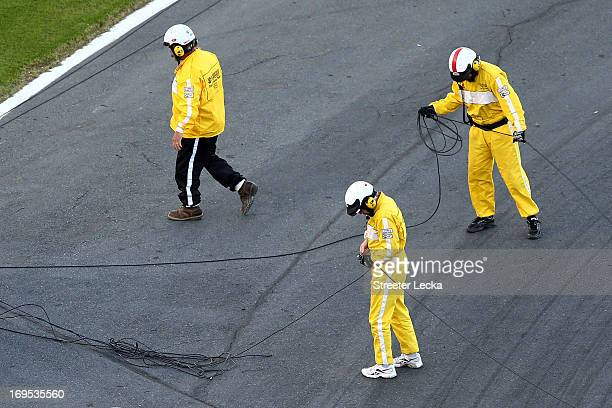 Track workers clean up cable from an aerial Fox Sports camera on the front stretch during a red flag in the NASCAR Sprint Cup Series Coca-Cola 600 at...