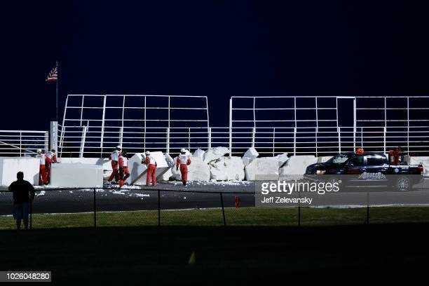 Track workers repair damage to a wall after a crash during the Toyota Mod Classic 150 at Oswego Speedway on September 1 2018 in Oswego New York