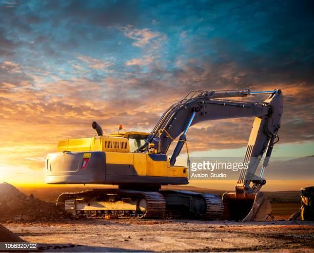 escavadeira controlada no local da construção à noite. - escavadora mecânica - fotografias e filmes do acervo