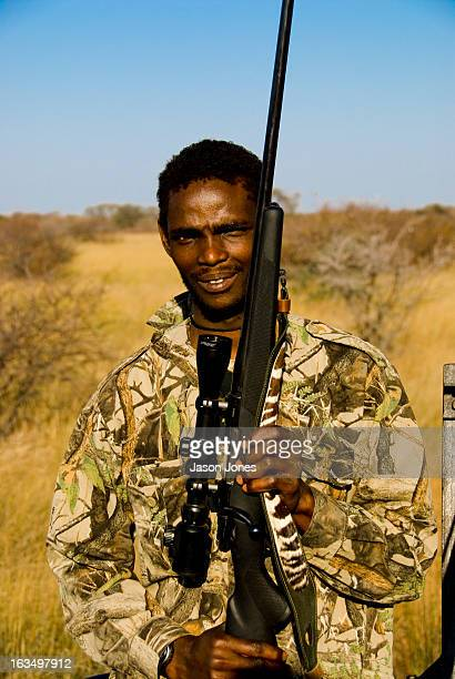 Tracker and guide holds a clients rifle at a game farm in Thabazimbi, South Africa