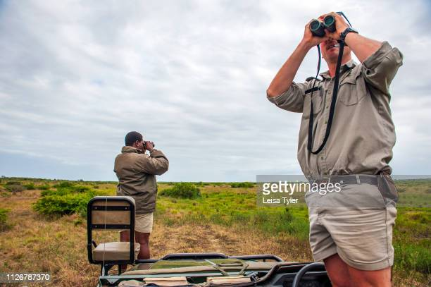 A tracker and guide looking for big game at the Phinda Private Game Reserve an andBeyond owned nature Hotel and safari owner and operator andBeyond...