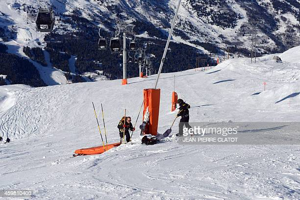 Trackers secure a pylon on December 31 2013 on a slope of the French Alps ski resort of Meribel not far from the site where German retired Formula...