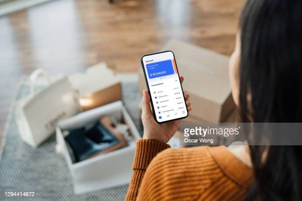 tracking bank account transactions with mobile banking - buying stock pictures, royalty-free photos & images