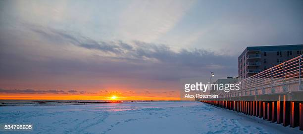 tracks on snowy ground at sunset on long beach next to wall. - nassau stock photos and pictures