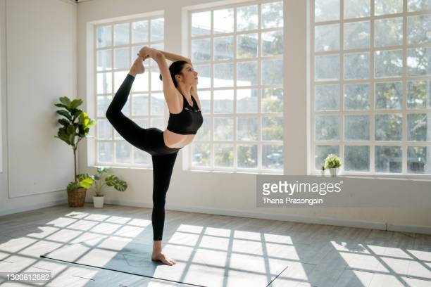 tractive young woman doing ballet in gyme and smiling - warming up stock pictures, royalty-free photos & images