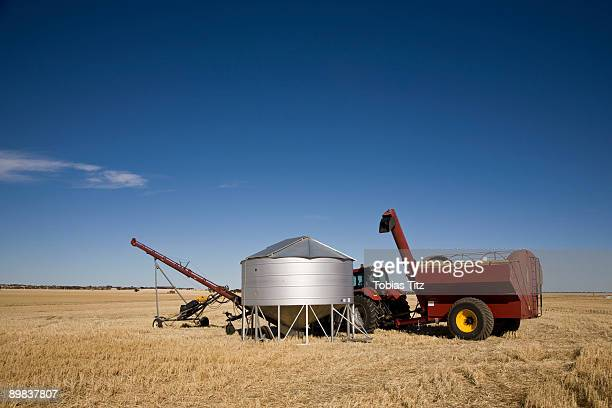 A tractor and combine next to a seed container in a wheat field