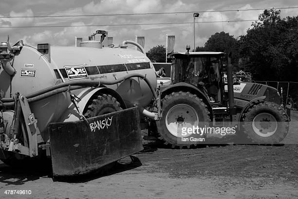 A tractor and tanker drive through the interstage area at the Glastonbury Festival at Worthy Farm Pilton on June 27 2015 in Glastonbury England Now...