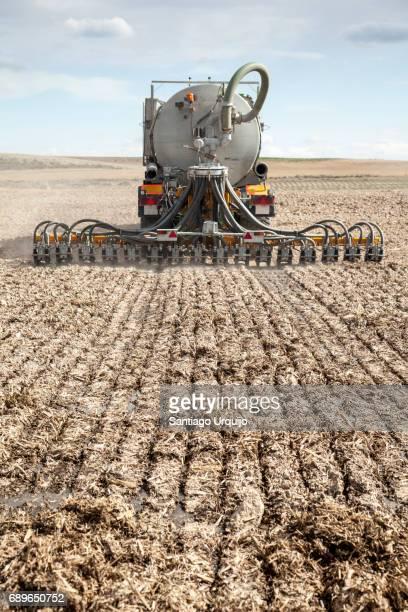 Tractor applying pig slurry on a field
