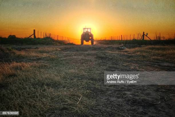 tractor at farm field against clear sky during sunset - andres ruffo fotografías e imágenes de stock