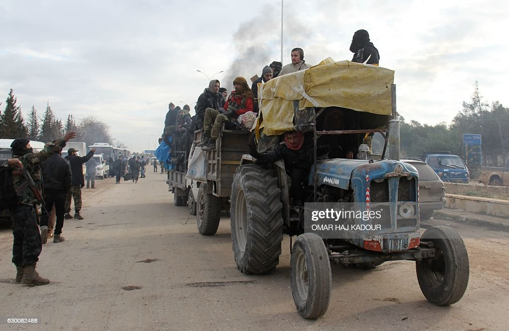 TOPSHOT - A tractor carrying people who were evacuated from rebel-held neighbourhoods in the embattled city of Aleppo arrive in the opposition-controlled Khan al-Aassal region, west of the embattled city, on December 16, 2016. The Syrian government suspended the evacuation of civilians and fighters from the last rebel-held parts of Aleppo, leaving thousands of people trapped and uncertain of their fate. The Syrian Observatory for Human Rights, a Britain-based monitor, estimated some 8,500 people had left before the operation was suspended, including around 3,000 rebel fighters. Syrian state media reported a figure of around 8,000. / AFP / Omar haj kadour