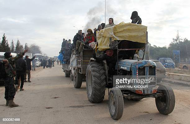 TOPSHOT A tractor carrying people who were evacuated from rebelheld neighbourhoods in the embattled city of Aleppo arrive in the oppositioncontrolled...