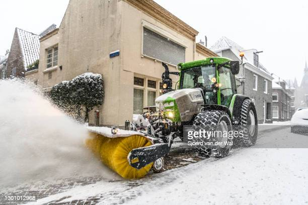 Tractor clearing the streets of snow with a snow plow and brush after heavy snowfall in the streets of Zwolle during a cold winter day in The...