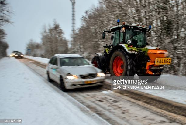 Tractor clears snow and spreads salt on a snowy road near the French border with Luxembourg on January 30, 2019 in Zoufftgen.