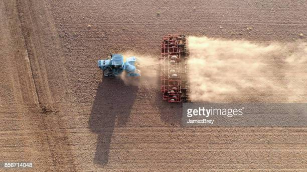 Tractor cultivating field, kicking up rocks and dust at dawn