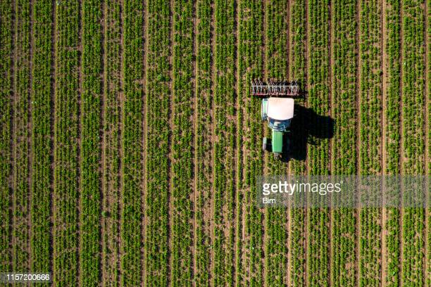 tractor cultivating field, view from above - crop stock pictures, royalty-free photos & images