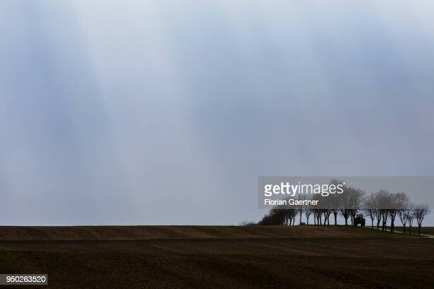 A tractor drives along a track across the fields on April 13 2018 in Zittau Deutschland