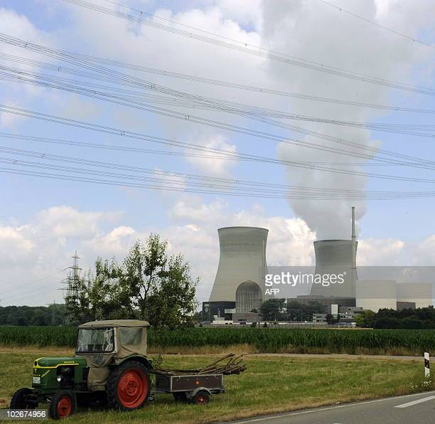 A tractor drives in the foreground of the cooling towers of the nuclear power station in Gundremmingen southern Germany can be seen on July 6 2010...