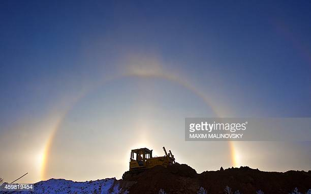 A tractor drives past the halo of a winter rainbow on a very cold day in the field outside Minsk on December 2 2014 The halo is an optical phenomenon...