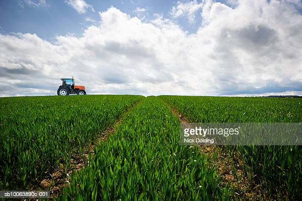 tractor driving along crop field, side view - tractor stock pictures, royalty-free photos & images