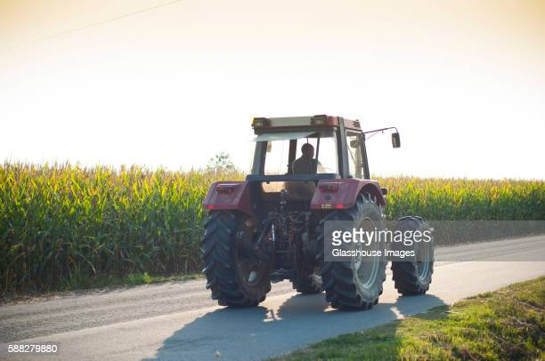 tractor driving on rural road - tractor stockfoto's en -beelden