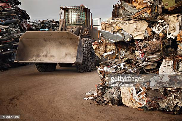 A tractor driving through stacks of compacted rubbish