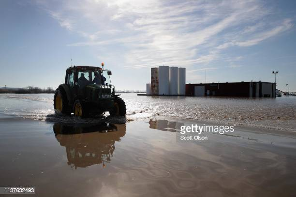 CRAIG MISSOURI MARCH 22 A tractor heads down a flooded Highway 59 on March 22 2019 near Craig Missouri Midwest states are battling some of the worst...