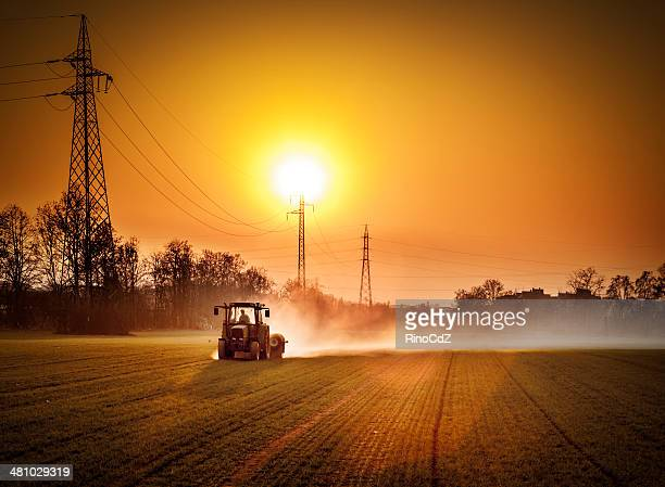 tractor in a field at sunset - tractor stock pictures, royalty-free photos & images